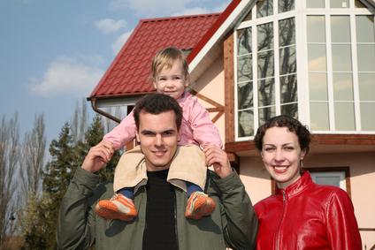 Family with baby and house